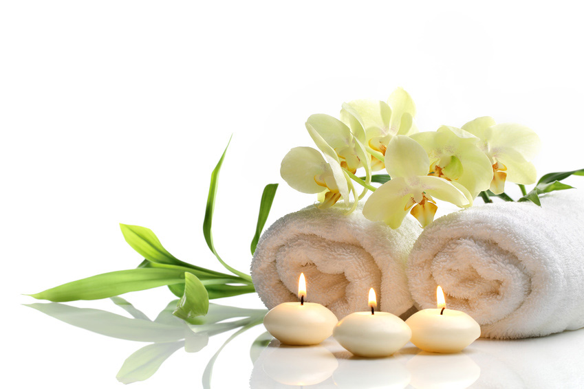 Spa still life with towel, burning candles and flower on white background.